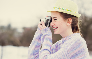 cheerful girl photographer takes on an old camera in winter
