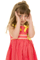 young girl in red dress hands by eyes