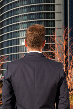 Back View of a Elegant Businessman with a Big Building at Backgr