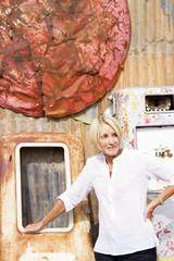 Mature Woman Among Rusting Metal in Junk Yard