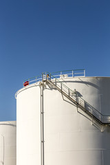 white tanks in tank farm with iron staircase