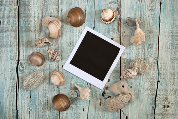 Sea shells and instant photo frame on old wooden table