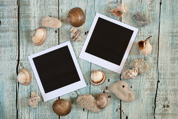 Sea shells and instant photo frames on old wooden table