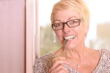 Lächelnde Rentnerin beißt mit gesunden Zähnen auf eine Gabel