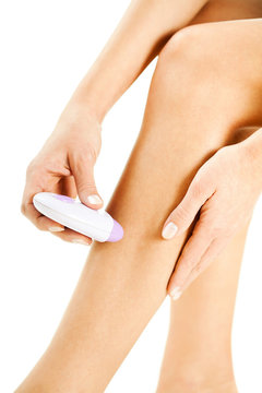 Woman shaving legs with electric shaver