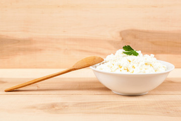 Fresh cottage cheese in a white bowl with spoon on a wooden.