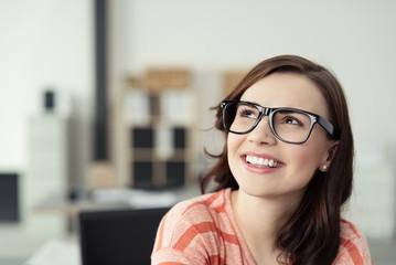 zufriedene junge frau im büro schaut lächelnd nach oben