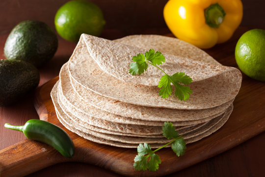 whole wheat tortillas on wooden board and vegetables