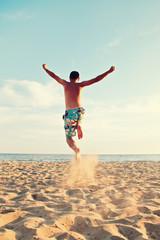 man jumping at beach - summer holidays