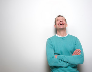 Man laughing with arms crossed and looking up