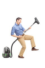 Young man playing guitar on a vacuum cleaner