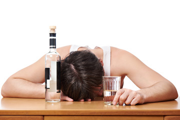 Drunk man asleep at table with glass of vodka