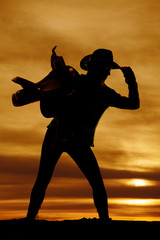 silhouette of a woman with a saddle on her shoulder touch hat