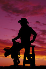 silhouette of  woman with a saddle on her knee look to side
