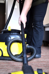 Maid cleaning the carpet with vacuum cleaner