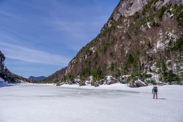 man trekking across a frozen lake
