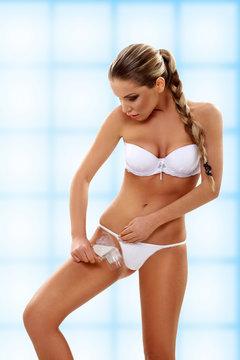 Woman depilating bikini line by waxing
