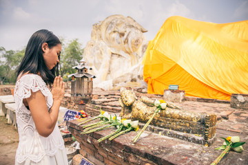 Woman praying at Buddha statue