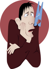 Nasal congestion. Man with a clothespin on his nose