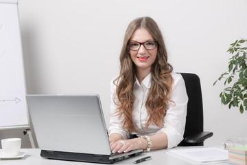Junge Frau lächelt am Computer