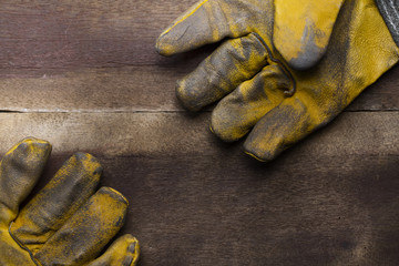 old dirty leather work gloves on wood background