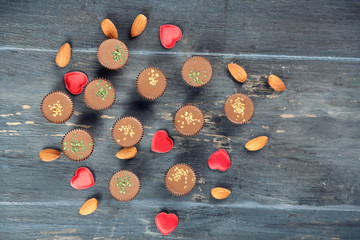 Tasty chocolate candies with almond and hearts on wooden table