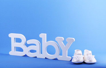 Word baby and booties on blue background