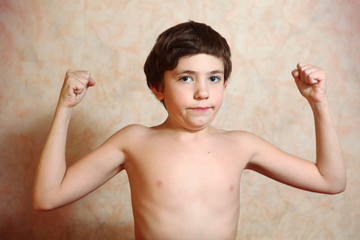 preteen handsome boy try to show his biceps muscles