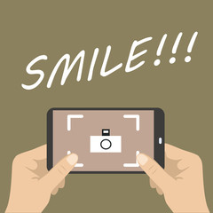 Human hands holding mobile phone camera with Smile!