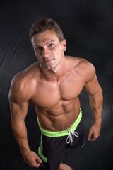 Handsome shirtless bodybuilder shot from above, standing