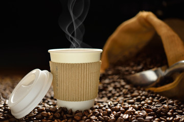 Paper cup of coffee with smoke and coffee beans on wooden table