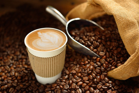 Paper cup of coffee latte and coffee beans on wooden table