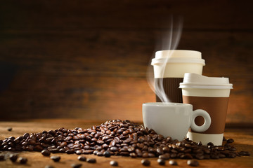 Cups of coffee and coffee beans on old wooden background