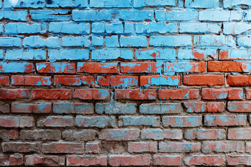 Old red brick wall half painted in bright blue color a lot of