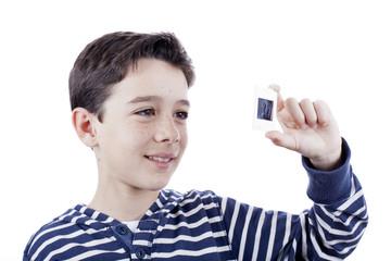 Niño sonriendo mirando diapositiva al trasluz