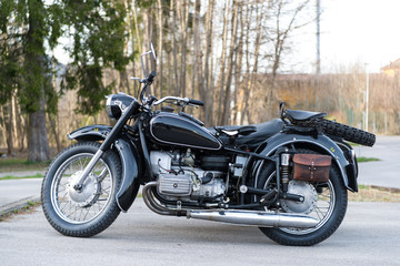 sideview of black oldtimer motorbike with sidecar an leather bag