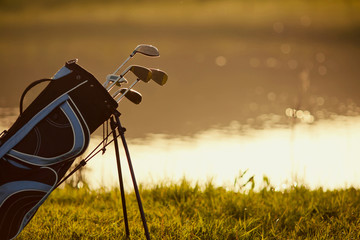 Golf clubs on grass and lake background