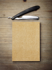 Straight razor and kraft paper on wood desk