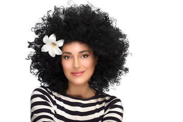 Fashion Brunette Girl with Flower in Curly Afro Hairstyle