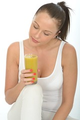 Healthy Young Woman Holding a Glass of Lime and Mango Smoothie