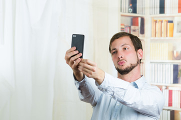 attractive young man using cell phone to take a selfie