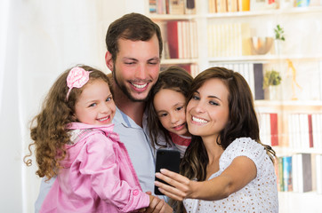 Cute family with two little girls taking a selfie photo