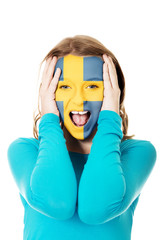 Woman with Sweden flag on face.