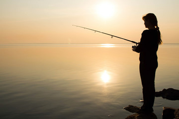 silhouette of a young girl fishing at sunset near the sea