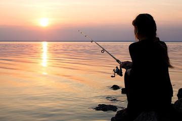Printed kitchen splashbacks Fishing young girl fishing at sunset near the sea