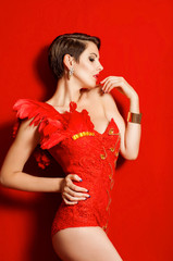 Young beautiful girl in a dancing suit with red feathers
