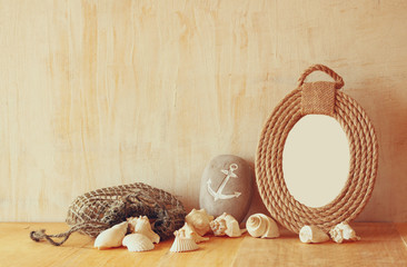 Vintage nautical frame from ropes and natural seashells on woode