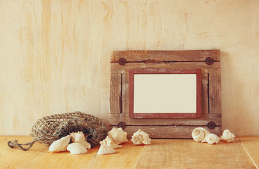 Old nautical wooden frame and natural seashells on wooden table
