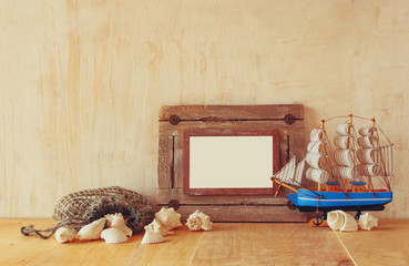 Old nautical wooden frame, boat and natural seashells on wooden