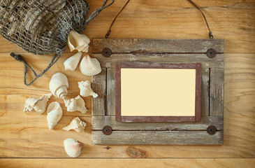 Top view of old nautical wooden frame and natural seashells on w
